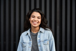 Smiling African American young woman wearing denim jacket laughing looking at camera standing on black background. Happy positive mixed race teen generation z hipster girl posing for portrait.