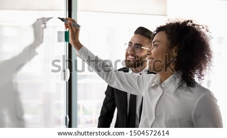 Smiling african and arabian ethnicity entrepreneurs using flip chart create successful business plan, market research and analysis, executive summary, start up ideas concept, horizontal banner image