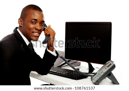 Smiling african businessman communicating on phone looking at camera