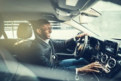 Smiling African businessman wearing a blazer changing stations while driving his car through the city during his morning commute to work