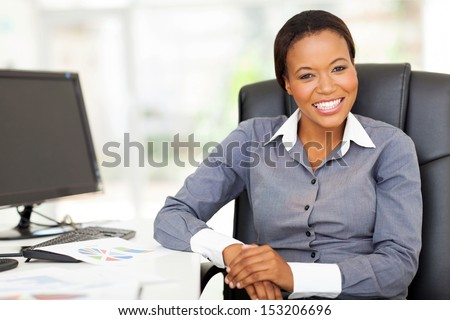 smiling african businesswoman sitting in office looking at the camera