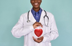 Smiling African female doctor wear white lab coat, stethoscope holding red heart in hands. Cardiology healthcare, love medicine charity, healthy heart protection, cardiac diseases concept, close up.