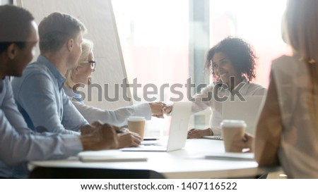 Smiling african female leader handshake partner client making commercial deal agreement at team meeting or group negotiations sitting at conference table shake hands thank for collaboration, respect