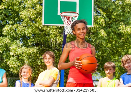 Smiling African girl with ball and friends behind