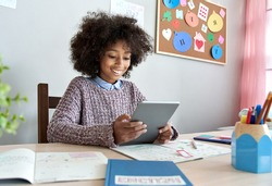 Smiling african kid girl holding digital tablet elearning. Happy mixed race school child using device remote social distance learning watching virtual lesson class online. Children learning at home.
