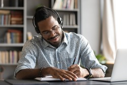 Smiling african male student professional wear headset elearning study with online tutor teacher listening audio podcast e learning language concept make notes sit at home office desk with laptop