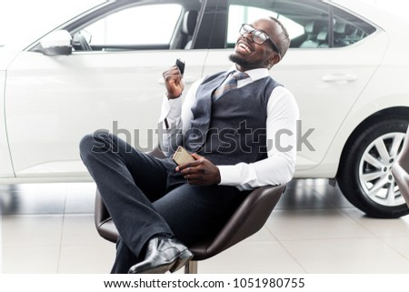 Smiling African man sitting on the background of a new car in the showroom