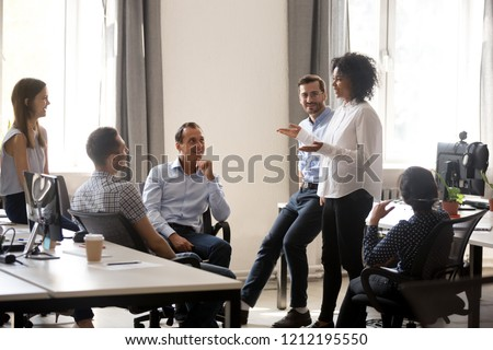 Smiling african manager coach speaking at diverse corporate group meeting, female black teacher team leader talking to office workers at training teaching employees explaining new idea, mentoring