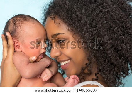 Smiling African mother holding her 11 days old newborn baby