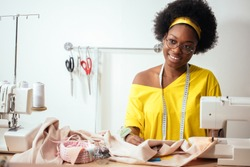 smiling african seamstress looking at camera with sewing machine
