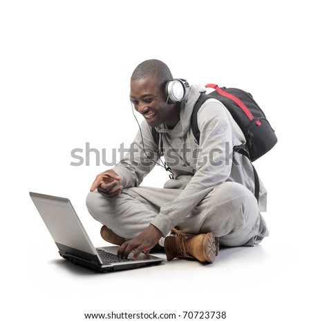 Smiling african student using a laptop