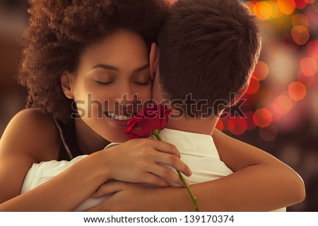 Smiling African woman hugging her boyfriend and holding the rose she got for Valentine\'s Day.