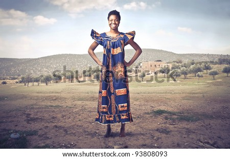 Smiling african woman in traditional clothes on a desert field