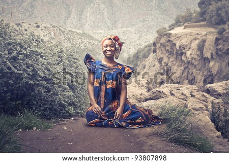 Smiling african woman in traditional clothes sitting on a rock