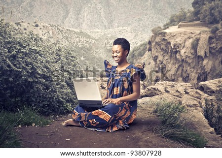 Smiling african woman in traditional clothes sitting on a rock and using a laptop