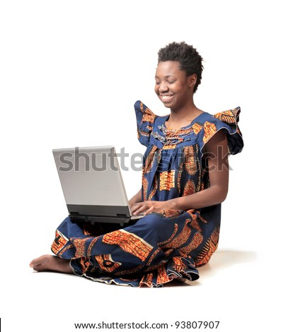 Smiling african woman in traditional clothes using a laptop