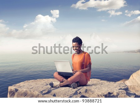 Smiling african woman using a laptop with seascape in the background
