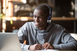 Smiling african young man student wear headphones looking at laptop screen writing notes, happy black guy e-learning in internet study online with teacher on computer watch webinar sit in cafe