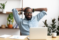 Smiling Afro-American businessman holding hands behind head sitting at office desk behind laptop. Happy black employee feeling no stress, relaxing, watching funny video after successful working