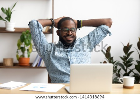 Photo of Smiling Afro-American businessman holding hands behind head sitting at office desk behind laptop. Happy black employee feeling no stress, relaxing, watching funny video after successful working