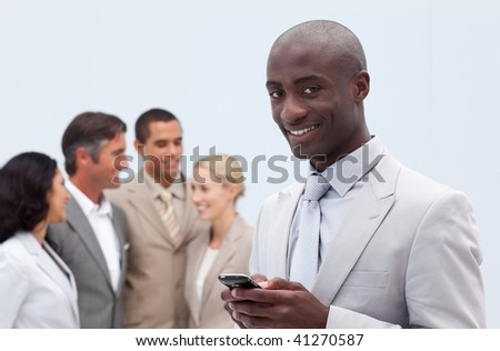 Smiling Afro-American businessman sending a message with a mobile phone