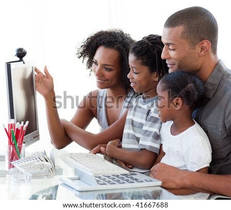 Smiling Afro-American family working with a computer at home