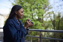 Smiling afro american hipster girl fond of photography preparing for taking picture on camera enjoying leisure, happy dark skinned photographer satisfied with working process outdoors in spring