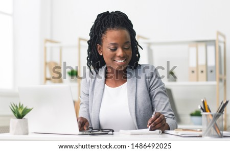 Smiling Afro Businesswoman Working On Laptop And Taking Notes In Modern Office. Free Space