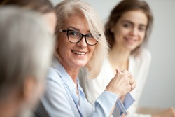 Smiling aged businesswoman in glasses looking at colleague at team meeting, happy attentive female team leader listening to new project idea, coach mentor teacher excited by interesting discussion