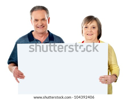 Smiling aged couple holding blank white poster showing it to camera