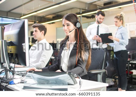Smiling agent woman with headsets helping a customer. Portrait of call center worker at office.