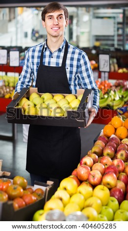smiling american  male seller posing with apples, tangerines and bananas in store #404605285