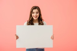 smiling and attractive woman holding empty board with copy space isolated on pink
