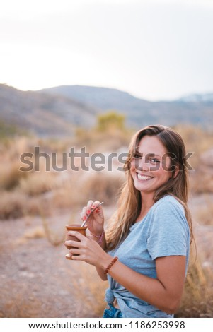 Smiling and attractive young woman drinking traditional Argentinian yerba mate tea from a calabash gourd with bombilla stick on a sunny day in the mountain.