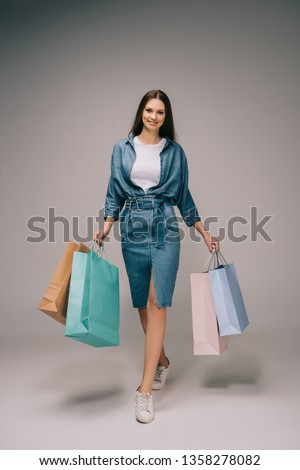 smiling and beautiful woman in denim dress holding shopping bags and looking at camera