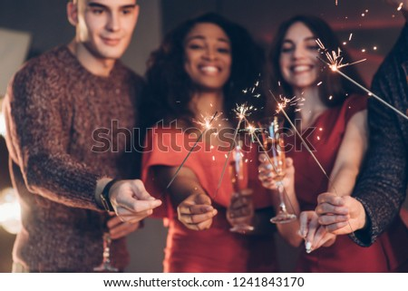 Smiling and feel happy. Multiracial friends celebrate new year and holding bengal lights and glasses with drink. #1241843170