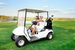 Smiling and happy couple driving a golf-cart with clubs on the back