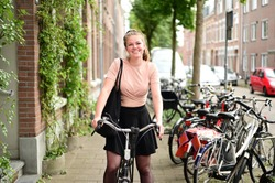 Smiling and happy Dutch student on a bicycle in a street with many bicycles in the Netherlands