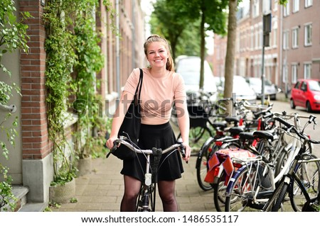 Smiling and happy Dutch student on a bicycle in a street with many bicycles in the Netherlands  Foto stock ©