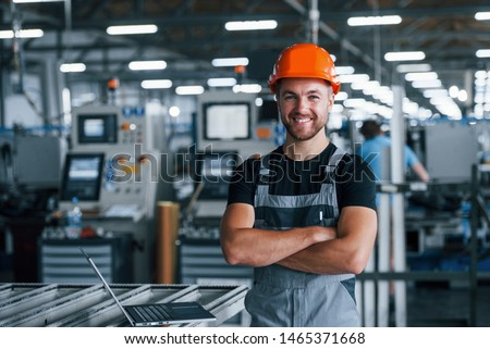 Smiling and happy employee. Industrial worker indoors in factory. Young technician with orange hard hat. Foto stock ©