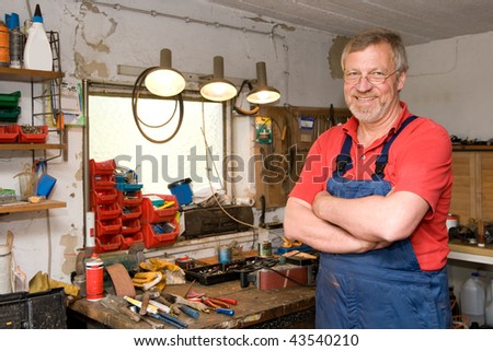 Smiling and happy senior craftsman in his garage
