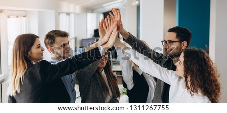 Smiling and laughing office working black and white men and women standing and giving high five to each other. #1311267755