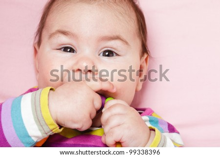 Smiling and playing baby with teething ring. Closeup face.