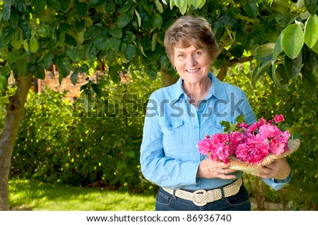 Smiling and Pretty Senior Woman Enjoying Her Garden and Holding a Bouquet of Pink or Red Roses that She Just Picked