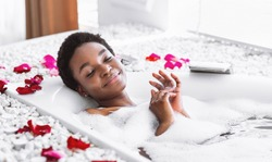 Smiling and relaxing african american woman with closed eyes takes bath with foam and petals