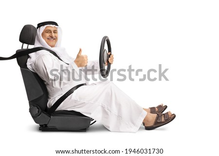 Smiling arab man in a driver seat holding the steering wheel and showing a thumb up sign isolated on white background Stockfoto ©