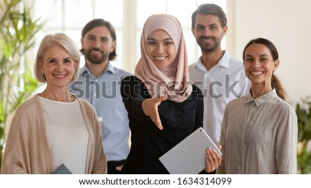 Smiling Arabian businesswoman stretch hand get acquainted greeting with client or customer pose together with diverse colleagues in office, happy multiracial employees look at camera show unity