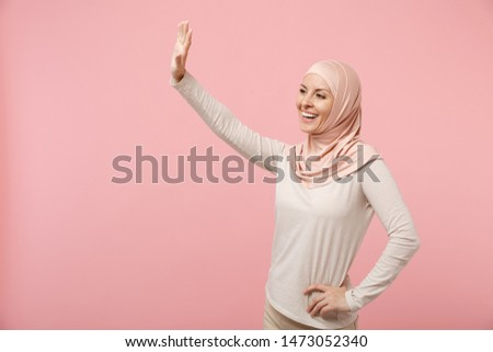 Smiling arabian muslim woman in hijab light clothes posing isolated on pink background. People religious Islam lifestyle concept. Mock up copy space. Waving and greeting with hand as notices someone #1473052340