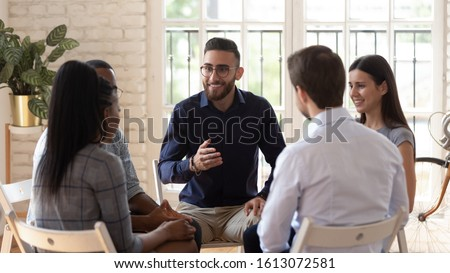 Smiling Arabic male mentor or coach sit in circle with diverse patients counseling help overcome life problems, multiethnic young people share thoughts speak at psychological therapy session