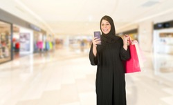 smiling Arabic woman shopping and using her smartphone